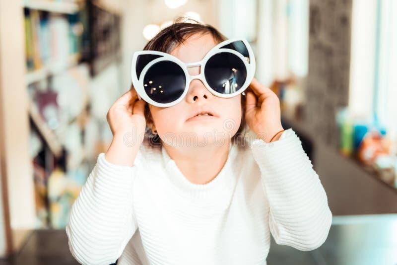 Peu enfant avec syndrome de Down utilisant de grandes lunettes de soleil en forme de chat photos libres de droits