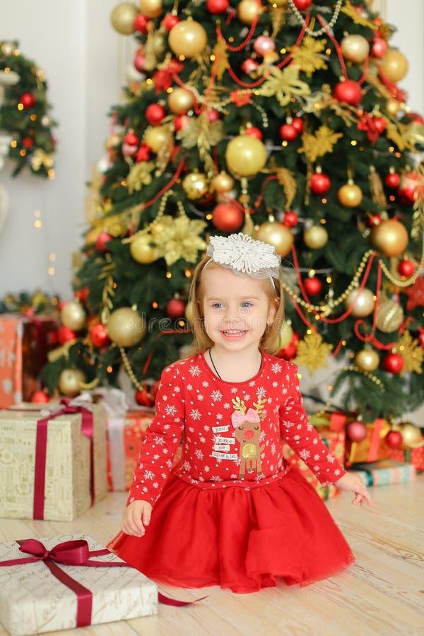 Peu enfant féminin de sourire portant la robe rouge se reposant sur le plancher près des cadeaux et de l'arbre de Noël photos stock