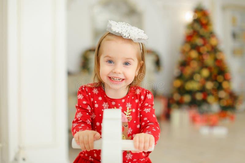 Peu enfant féminin jouant avec le cheval de basculage, arbre de Noël à l'arrière-plan brouillé images libres de droits