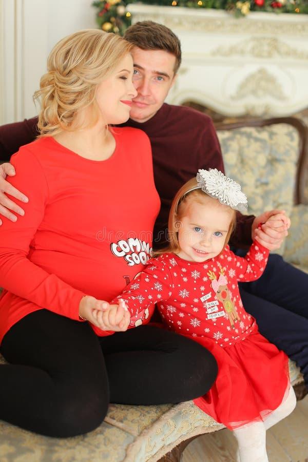 Peu enfant féminin s'asseyant avec le père et la mère enceinte près decoreated la cheminée photos libres de droits