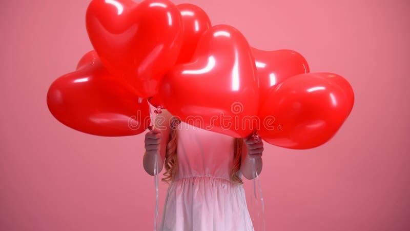 Peu enfant féminin se cachant derrière la surprise en forme de coeur de jour de valentines de ballons photos stock