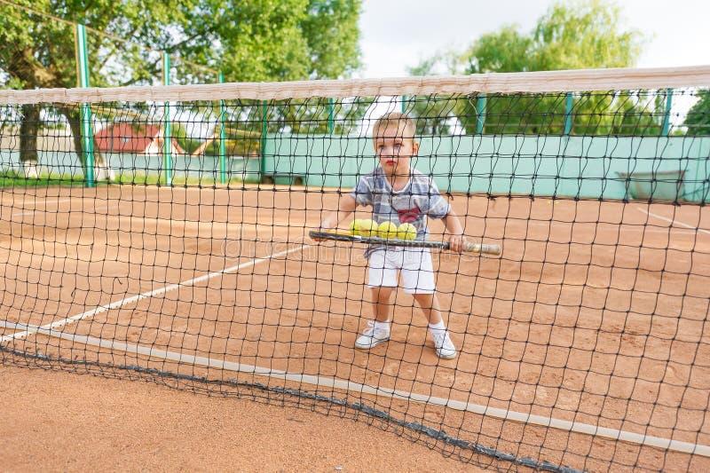 Peu enfant mignon jouant le tennis dehors au court de tennis photos libres de droits