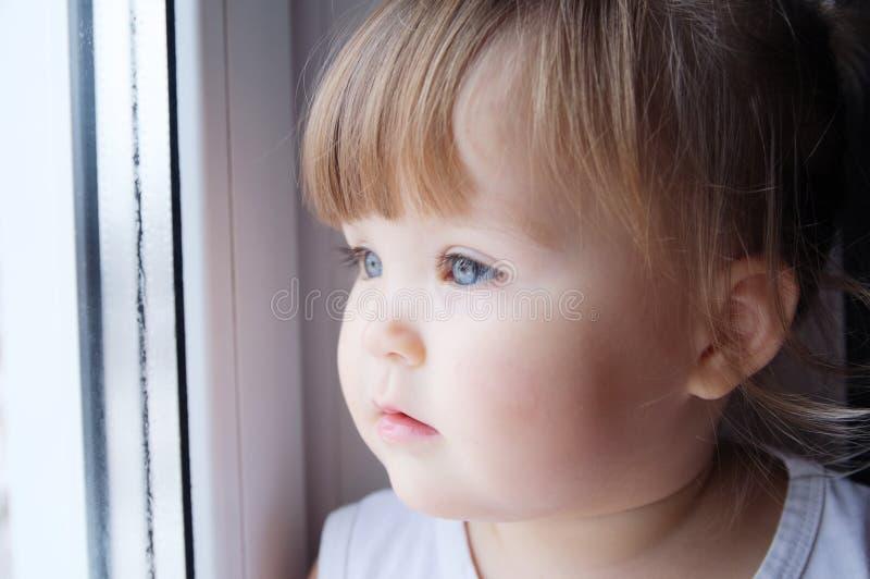 Peu enfant regardant la fenêtre bébé voulant marcher dehors au temps pluvieux photos stock