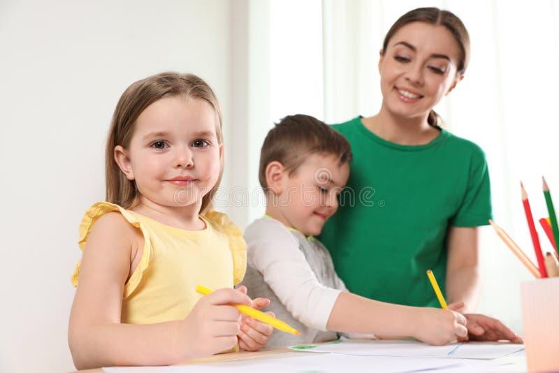Peu enfants avec le dessin d'institutrice gardienne à la table à l'intérieur photographie stock