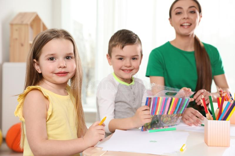 Peu enfants avec le dessin d'institutrice gardienne à la table ?tude et jouer image stock