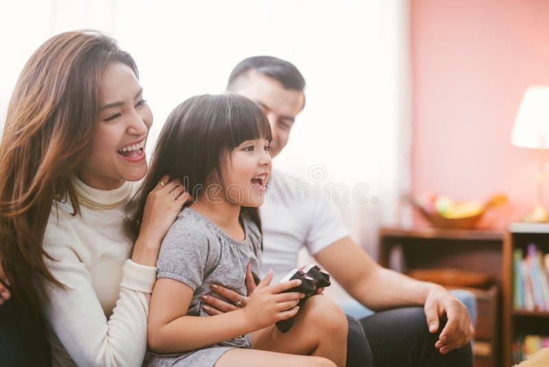 Peu famille de fille et de parent jouant le jeu vidéo à la maison photo libre de droits