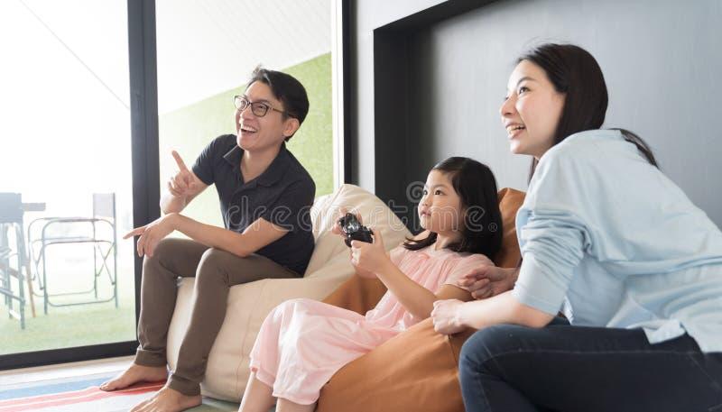 Peu famille de fille et de parent jouant le jeu vidéo à la maison photos libres de droits