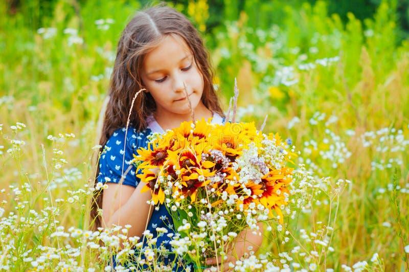 Peu fille adorable a recueilli un bouquet des fleurs sauvages photo stock