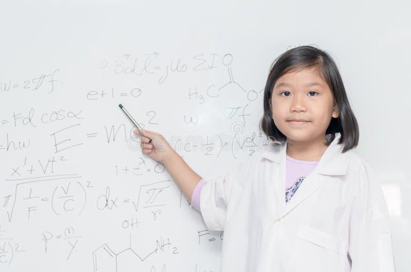 Peu fille asiatique de scientifique se dirigeant sur le conseil blanc images stock