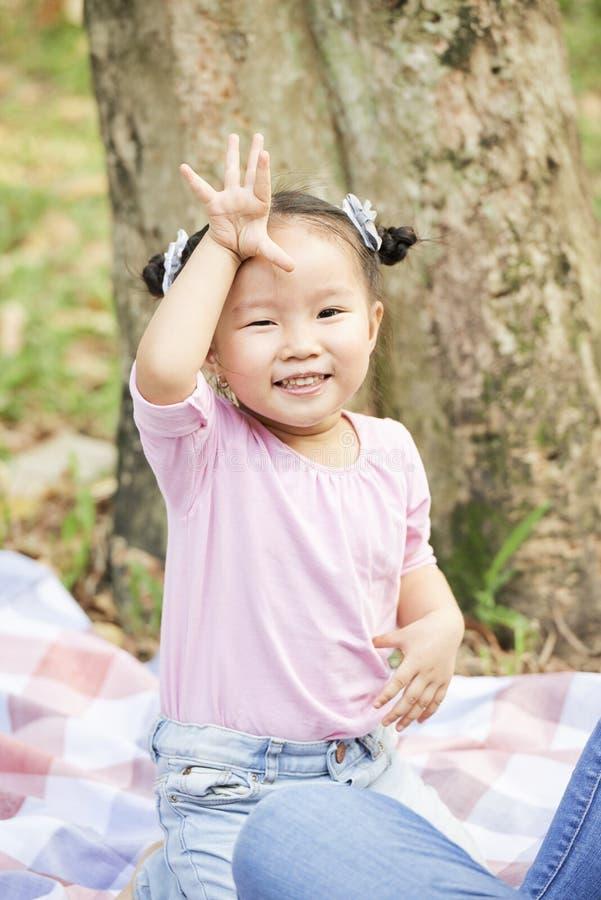 Peu fille asiatique disant au revoir photo libre de droits