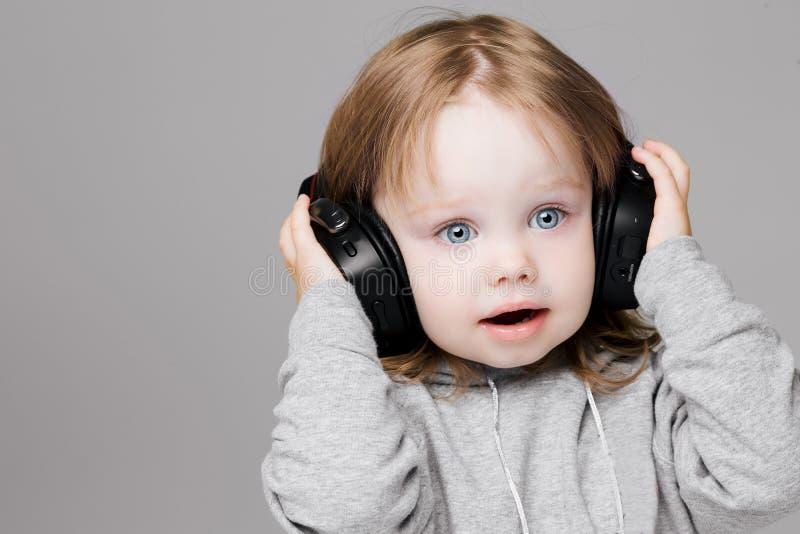 Peu fille avec la musique de écoute d'yeux bleus dans de grands écouteurs photo libre de droits