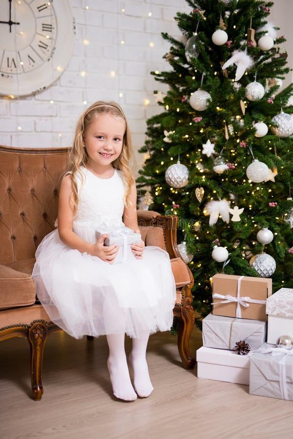 Peu fille avec le boîte-cadeau se reposant dans le salon avec Noël photographie stock