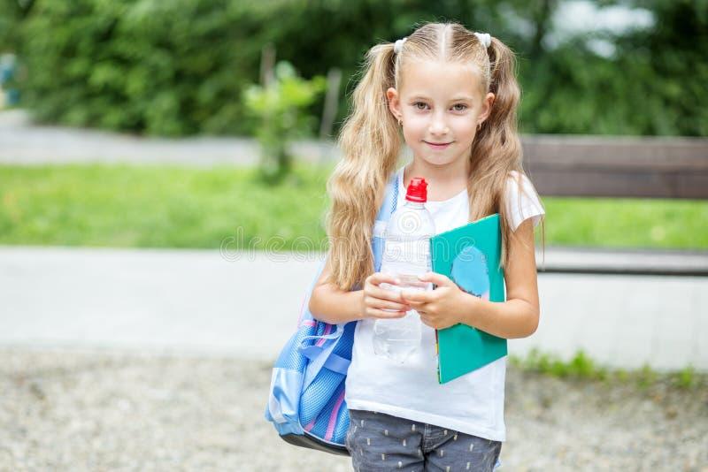 Peu fille avec le livre et le sac à dos en parc d'école Le concept de l'école, étude, éducation, amitié, enfance images stock