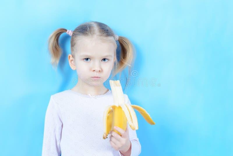 Peu fille avec les cheveux blonds sur un fond bleu L'enfant mange une banane photos libres de droits