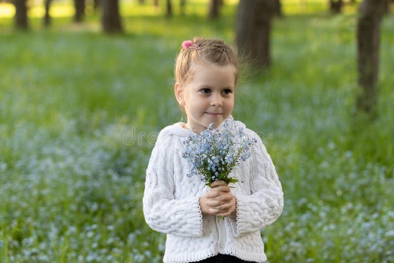 Peu fille avec un bouquet des myosotis des marais images stock