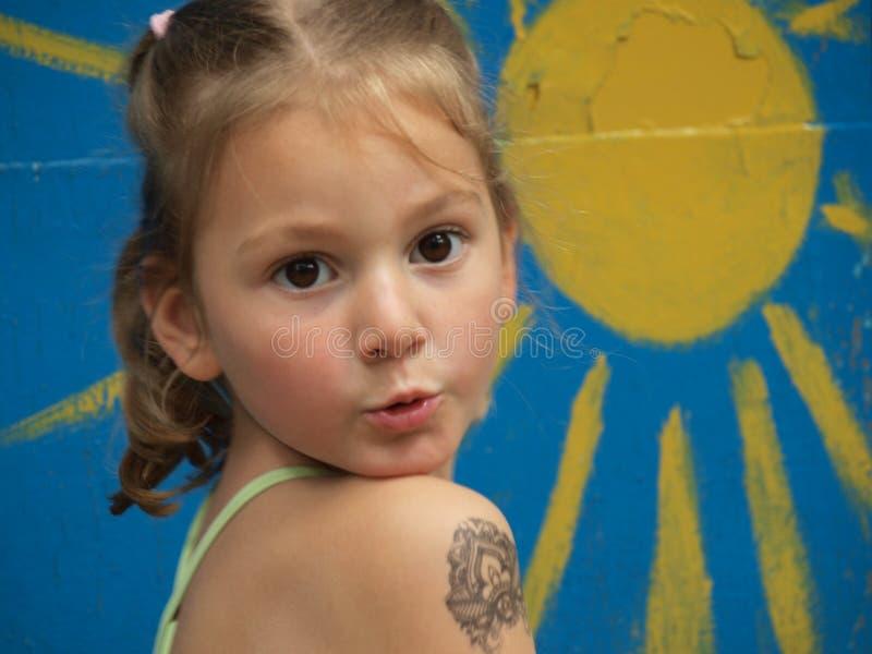 Peu fille avec un tatouage d'enfants sur son avant-bras sur le fond du soleil peint image stock