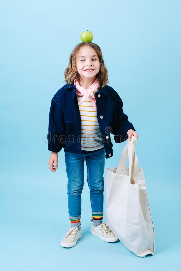 Peu fille avec une pomme sur sa tête tient le sac d'eco photographie stock