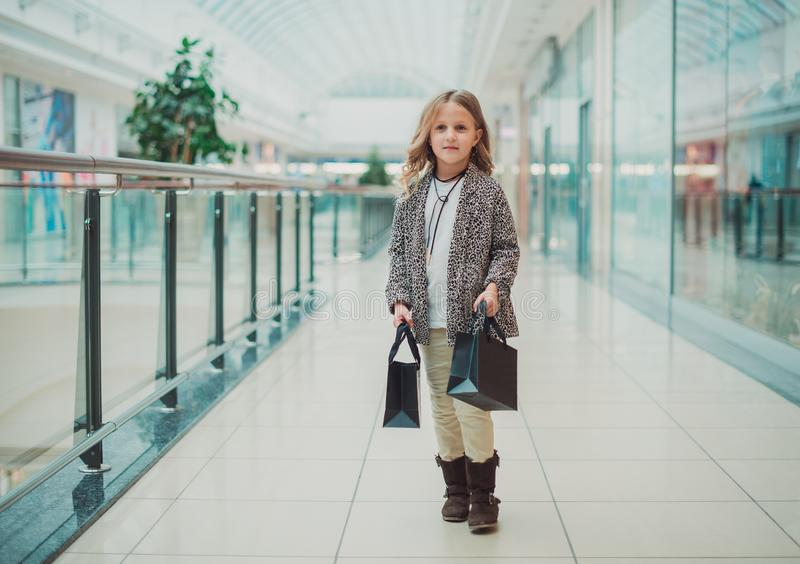 Peu fille blonde fait des emplettes au mail À côté des sacs noirs Concept noir de vendredi Vente dans les magasins photo libre de droits
