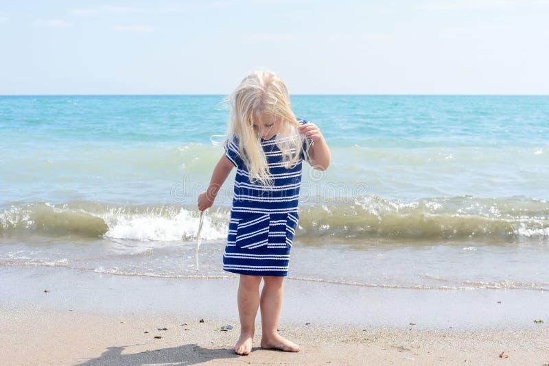 Peu fille blonde marchant sur la plage, tenant une plume photo stock