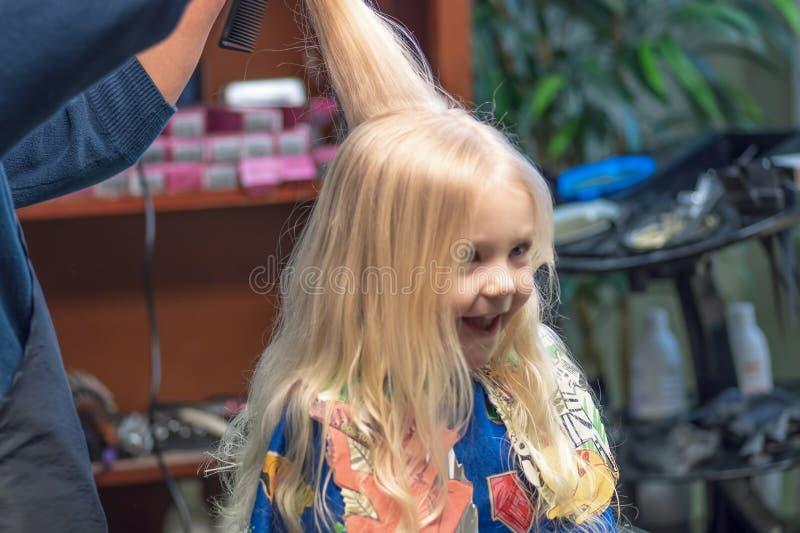 Peu fille blonde obtenant la première coupe de cheveux photo libre de droits