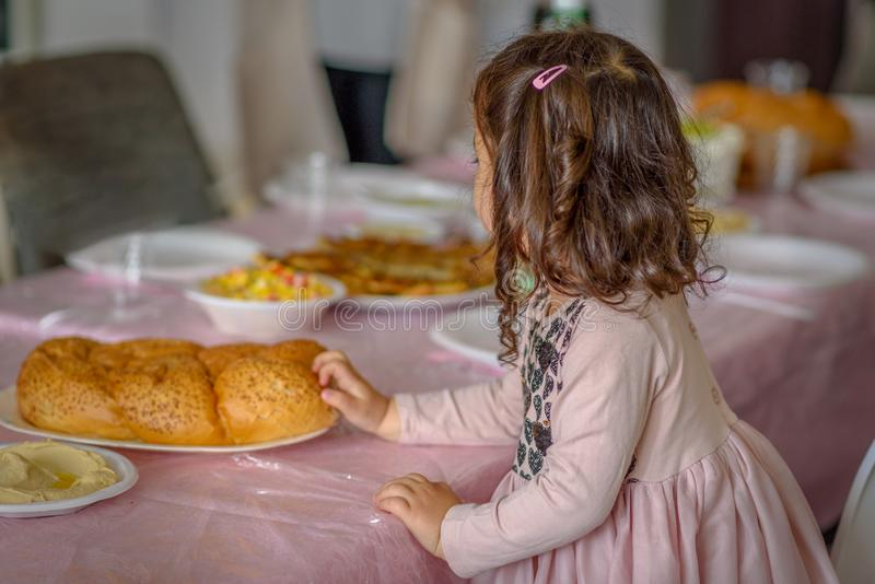 Peu fille bouclée plaçant le pain de pain du sabbat sur une table pour le repas de Shabbat image libre de droits