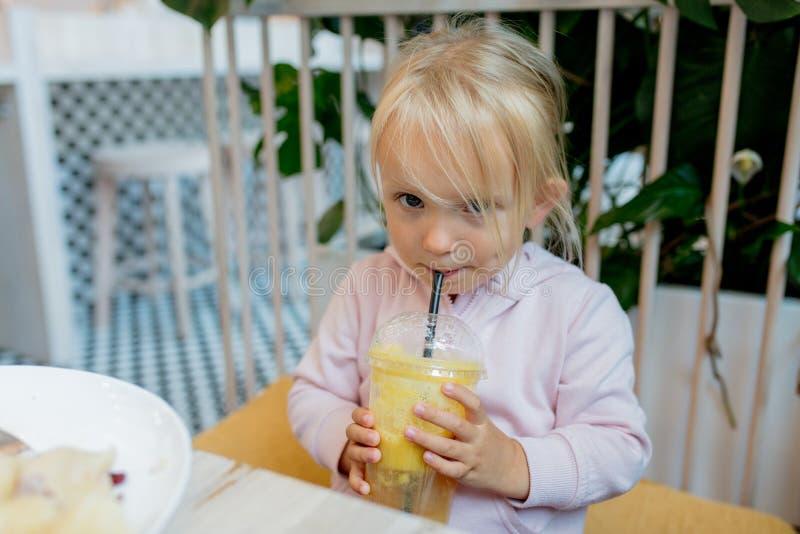 Peu fille buvant du jus d'orange dans un café images stock