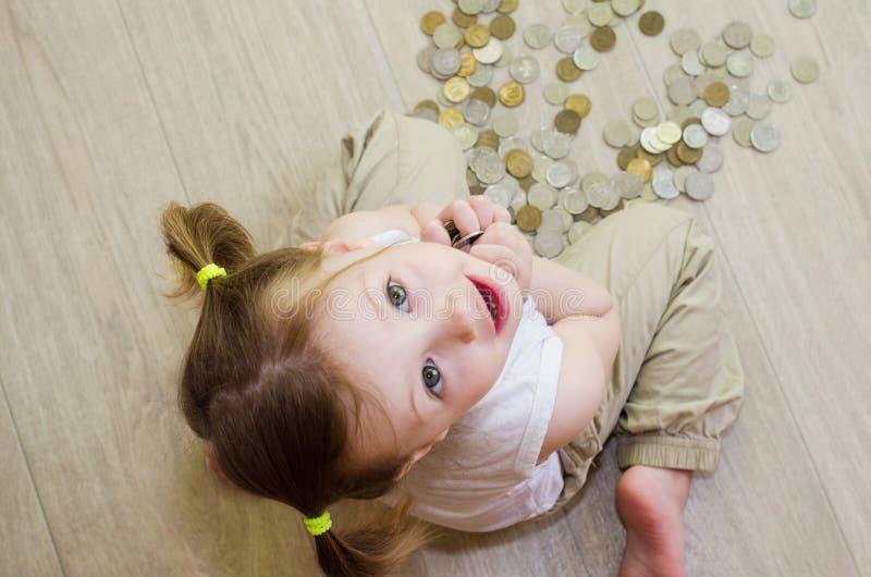 Peu fille comptant avec des pièces de monnaie image stock