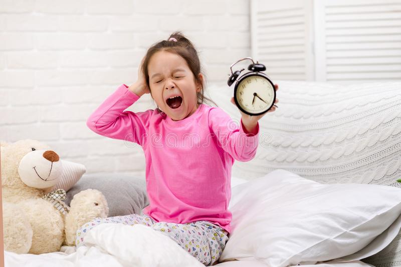 Peu fille dans des pyjamas avec l'horloge image stock