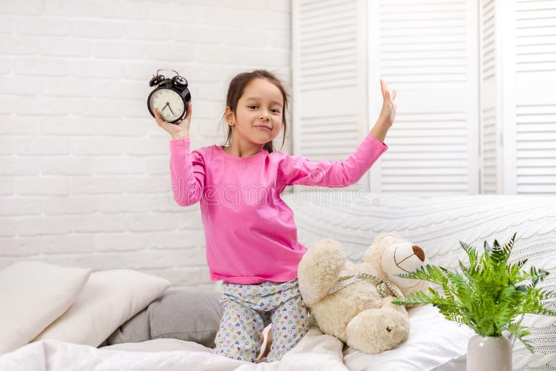 Peu fille dans des pyjamas avec l'horloge image libre de droits