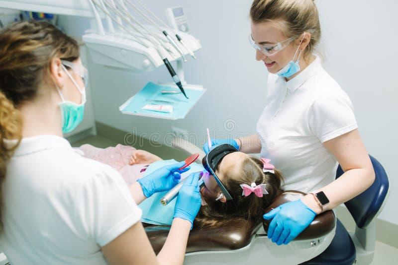 Peu fille dans des verres de VR et des ?couteurs sans fil se reposant dans la chaise dentaire Dentiste avec l'assistant photographie stock