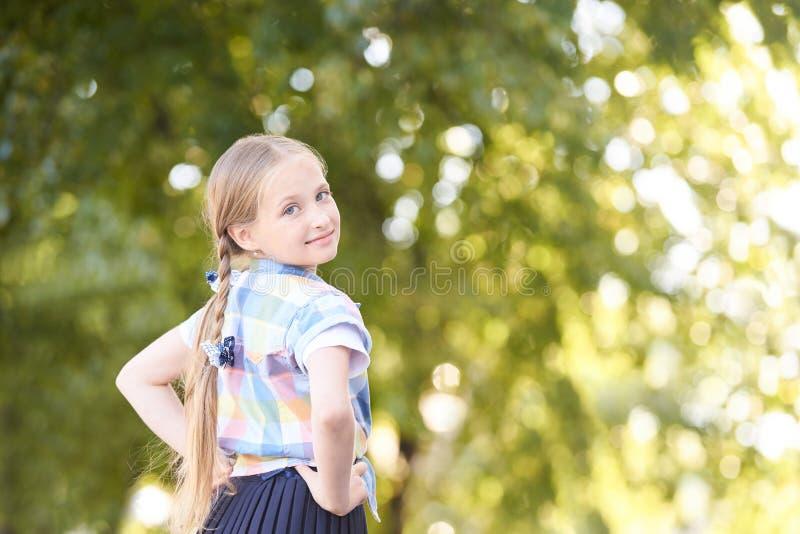 Peu fille dans la forêt ensoleillée verte le long Écolière d'amusement dehors Foyer s?lectif photographie stock libre de droits