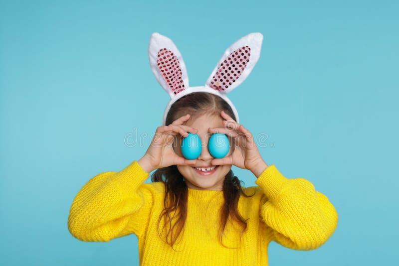 Peu fille dans le bandeau d'oreilles de lapin tenant des oeufs de pâques près des yeux photographie stock libre de droits