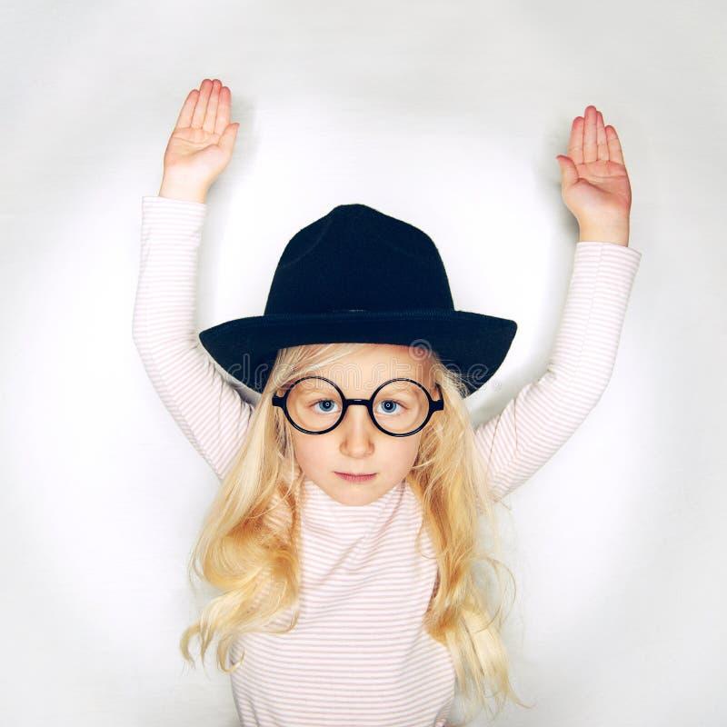 Peu fille dans le chapeau tenant des mains  photo stock