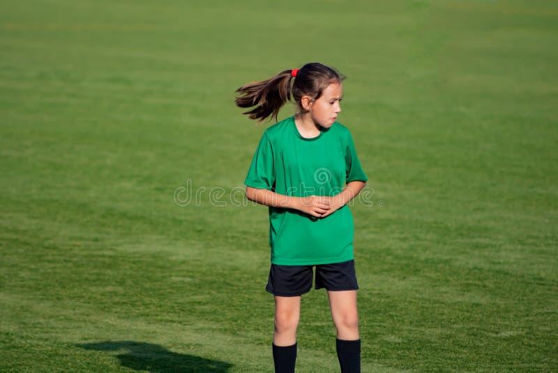 Peu fille dans une formation du football images stock
