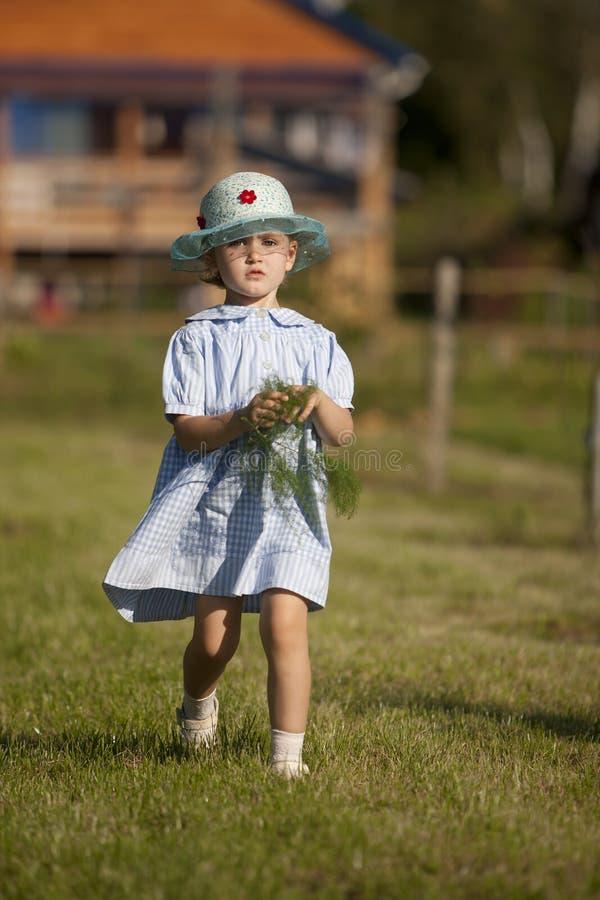 Peu fille dans une robe dans le style de la musique country dans le jardin d'été sur le fond de la maison de campagne photographie stock libre de droits