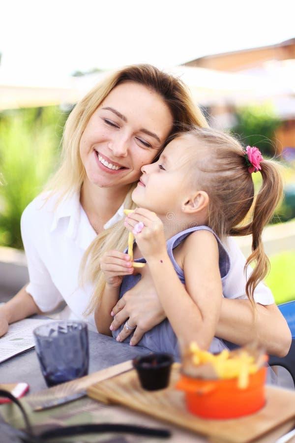 Peu fille embrassant la mère et s'asseyant au café de streeyt avec des pommes frites photos stock