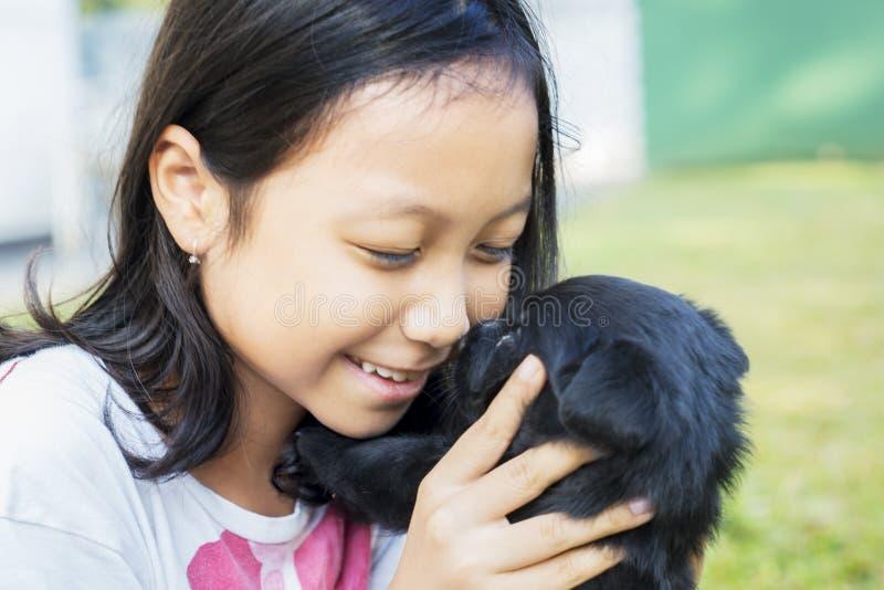 Peu fille embrassant son chiot sur la pelouse photos libres de droits