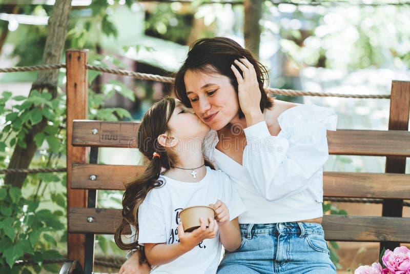 Peu fille embrasse la maman sur le banc image stock