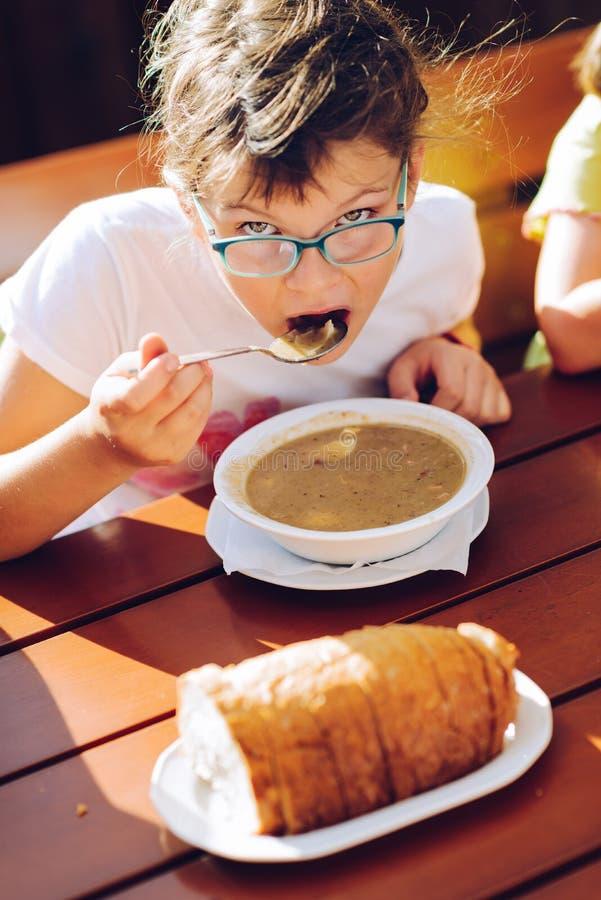 Peu fille en verres mangeant de la soupe chaude photo stock