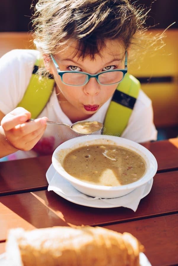 Peu fille - en verres - manger de la soupe chaude photos libres de droits