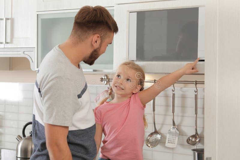 Peu fille et père utilisant le four à micro-ondes photo libre de droits