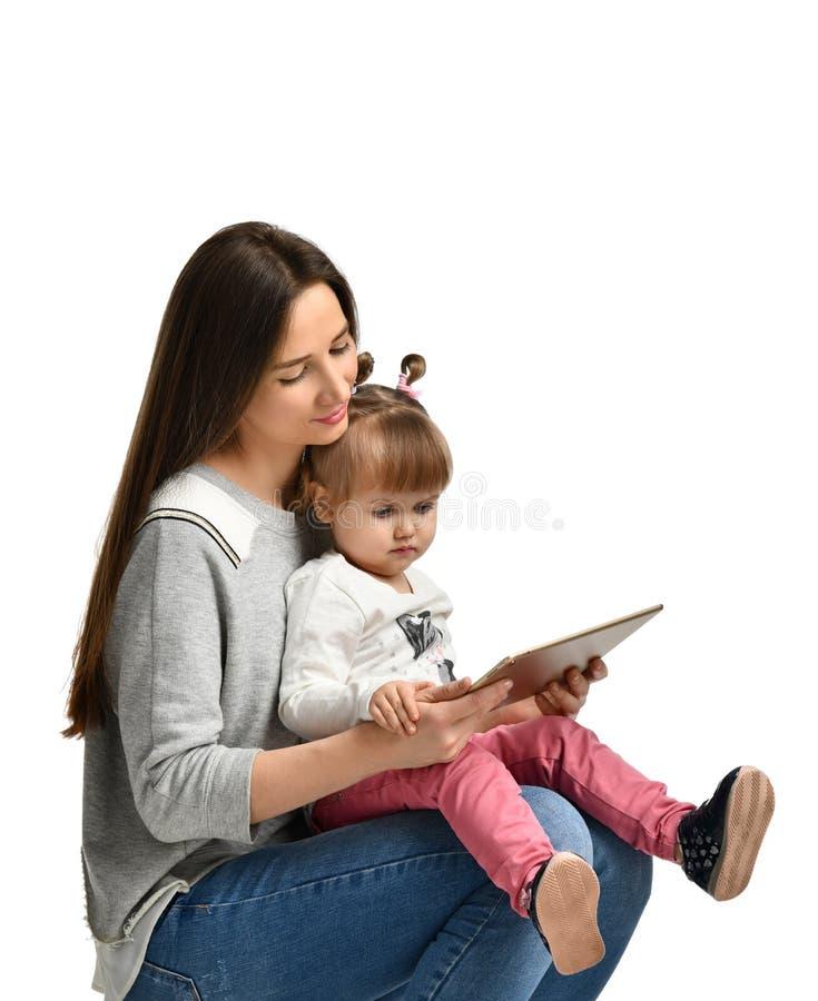Peu fille et sa belle jeune maman utilisent un comprimé numérique photos stock
