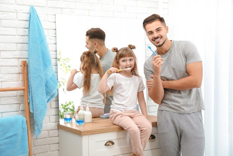 Peu fille et ses dents de brossage de père ensemble dans la salle de bains à la maison image stock
