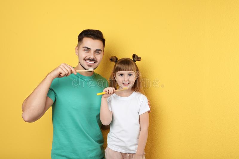 Peu fille et ses dents de brossage de père ensemble sur le fond de couleur photos stock