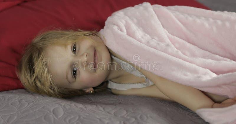 Peu fille gaie sous une couverture sur le lit ? la maison Assez, petite fille images libres de droits