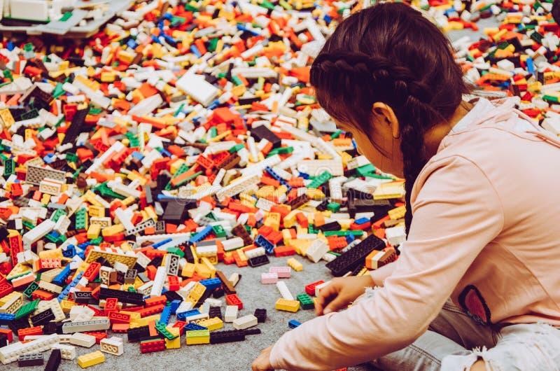 Peu fille jouant avec beaucoup de pièces de construction en plastique de briques image libre de droits