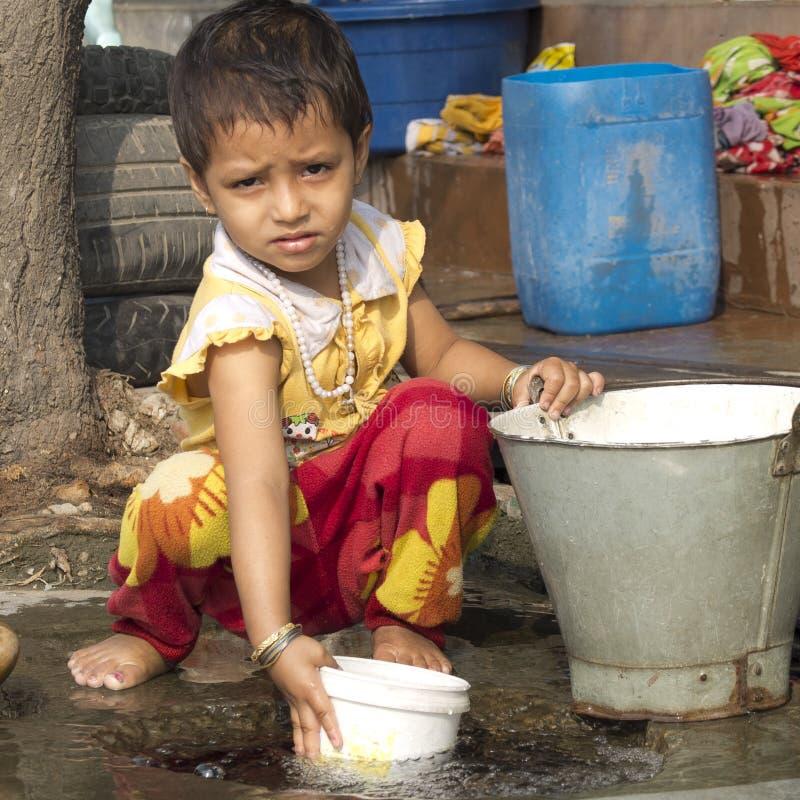 Peu fille jouant avec de l'eau dans la rue photos stock