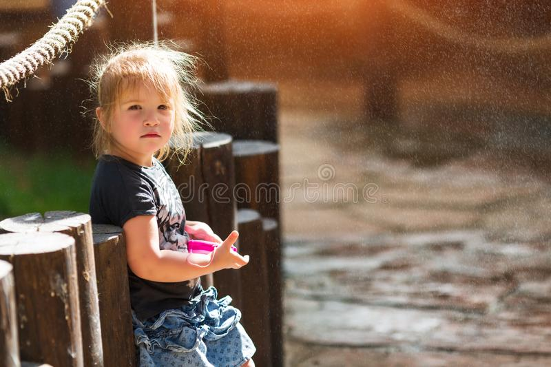 Peu fille jouant et ayant l'amusement appréciant le jet de la fontaine photos stock