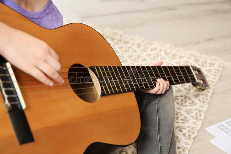 Peu fille jouant la guitare sur le plancher images libres de droits