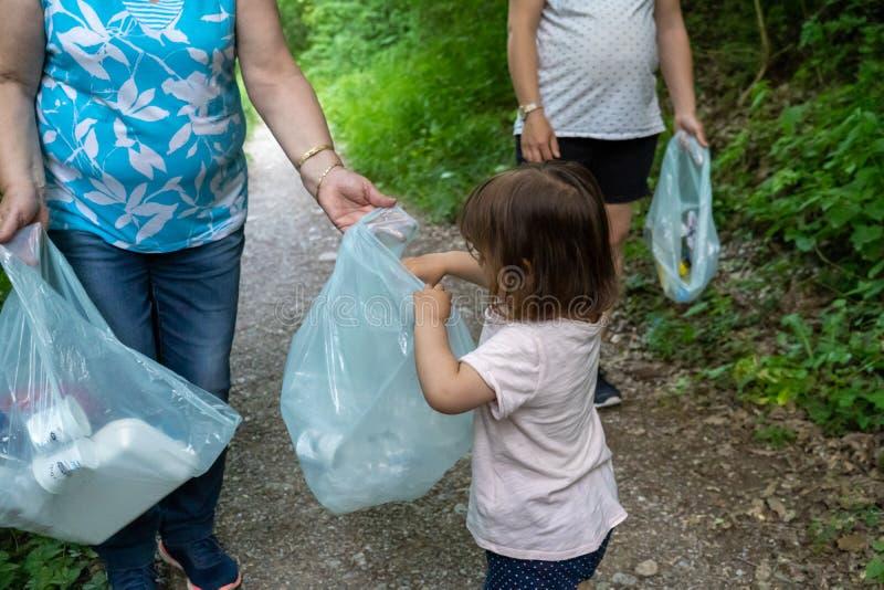 Peu fille, mère enceinte et grand-mère nettoyant la forêt de plastiques image libre de droits